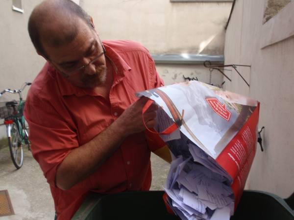 El traductor echando a la basura (reciclada, de papel), los manuscritos trabajados de la traducción de Abel.